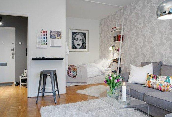 studio-meubles-gris-tapis-fourrure-gris-clair-sol-en-parqeut-clair-table-en-verre-transparente