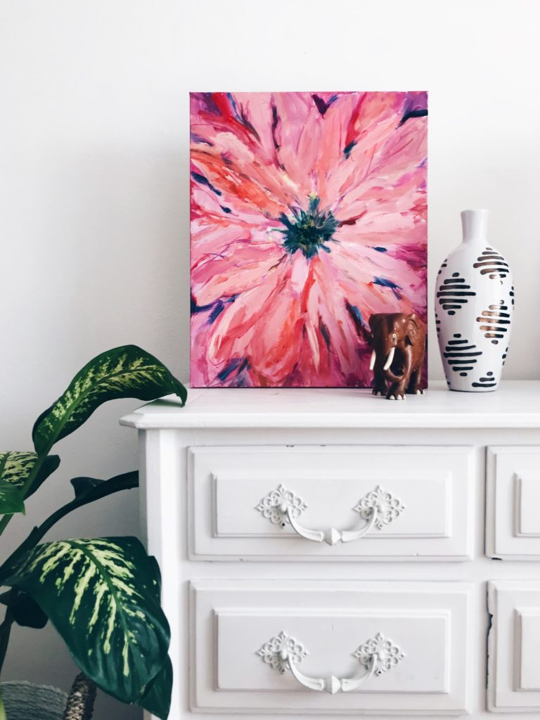 tableau représentant une fleur rose posé sur une commode